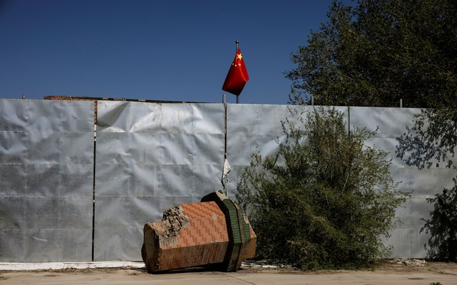 A part of a minaret broken off from the former Xinqu Mosque lies near a Chinese national flag in a yard adjacent to the former house of worship in Changji outside Urumqi, Xinjiang Uyghur Autonomous Region, China, May 6, 2021. REUTERS