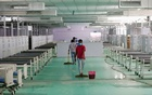 Workers clean the floor at the site of a temporary coronavirus disease (COVID-19) care facility, at Ramlila Ground, in New Delhi, India, May 12, 2021. REUTERS