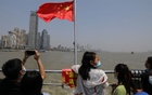 People stand near a Chinese national flag on a boat crossing Yangtze River, during the Labour Day holiday in Wuhan, Hubei province, China May 2, 2021. Reuters