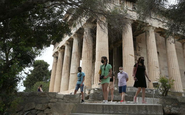 Tourists visit the ancient temple of Hephaestus, as the country's tourism season officially opens, in Athens, Greece May 15, 2021. REUTERS