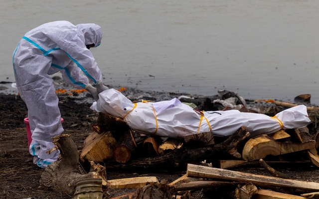A man wearing a protective suit touches the body of his relative, who died from the coronavirus disease (COVID-19), before his cremation on the banks of the river Ganges at Garhmukteshwar in the northern state of Uttar Pradesh, India, May 6, 2021. REUTERS