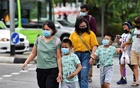 People wearing face masks cross a road amid the coronavirus disease (COVID-19) outbreak in Singapore May 14, 2021. REUTERS