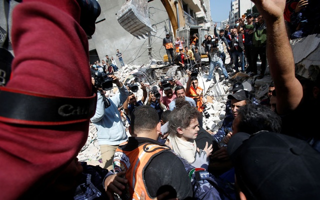 Rescuers carry Suzy Eshkuntana, 6, as they pull her from the rubble of a building at the site of Israeli air strikes, in Gaza City May 16, 2021. Reuters