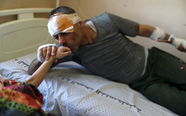 Riyad Eshkuntana kisses his daughter Suzy's hand as they are treated at a hospital after being pulled from the rubble of a building amidst Israeli air strikes, in Gaza City May 16, 2021. Reuters