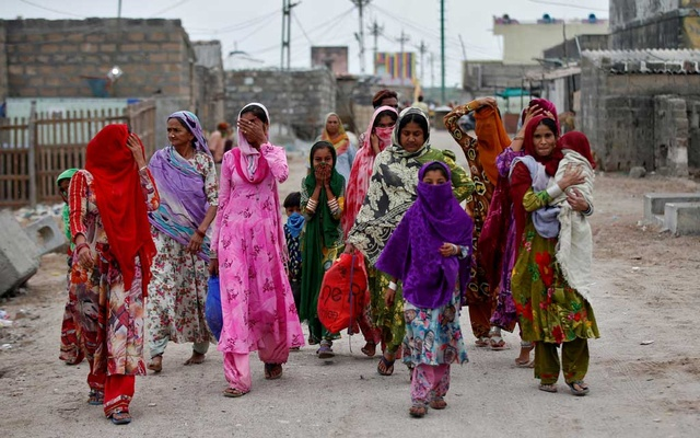 Women with their children leave their houses and evacuate to a safer place ahead of Cyclone Tauktae in Veraval in the western state of Gujarat, India, May 17, 2021. REUTERS