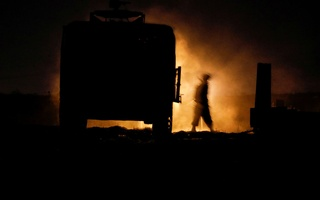 An Israeli soldier walks next to a military vehicle at a mobile artillery unit location on the Israeli side by the Israel border with Gaza May 16, 2021. REUTERS