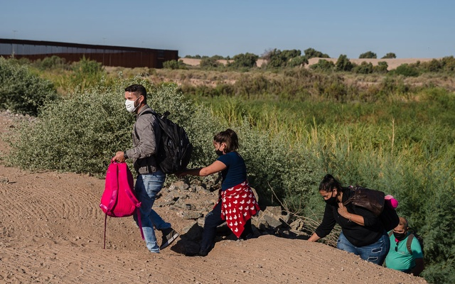 A family from Brazil walks up an embankment toward the border wall in Yuma, Ariz. on May 6, 2021. Fleeing virus-devastated economies, migrants are traveling long distances to reach the United States and then walking through gaps in the border wall. The Arizona desert has become a favourite crossing point. (Ariana Drehsler/The New York Times)