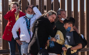 Natasha Gomez, who travelled with her family from Venezuela, cries near an opening in the border wall with Mexico in Yuma, Ariz., May 6, 2021. Fleeing virus-devastated economies, migrants are traveling long distances to reach the United States and then walking through gaps in the border wall. The Arizona desert has become a favourite crossing point. (Ariana Drehsler/The New York Times)