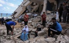 People sit amid the rubble of a home on Monday, May 17, 2021, which was bombed by Israeli army warplanes, in Gaza City, Gaza Strip. The New York Times