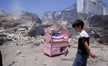 A Palestinian boy near the ruins of his house after an Israeli airstrike in Gaza City, Gaza Strip, May 14, 2021. Civilian deaths on both sides raise urgent questions about which military actions are legal, what war crimes are being committed and who, if anyone, will be held to account. (Samar Abu Elouf/The New York Times)