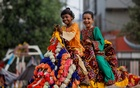 Siblings in new dresses react as they ride on a camel at a playground in a low-income neighbourhood as public places remain closed as preventive measures against the coronavirus disease (COVID-19) pandemic, during the second day of Eid-ul-Fitr celebrations, in Karachi, Pakistan May 14, 2021. REUTERS