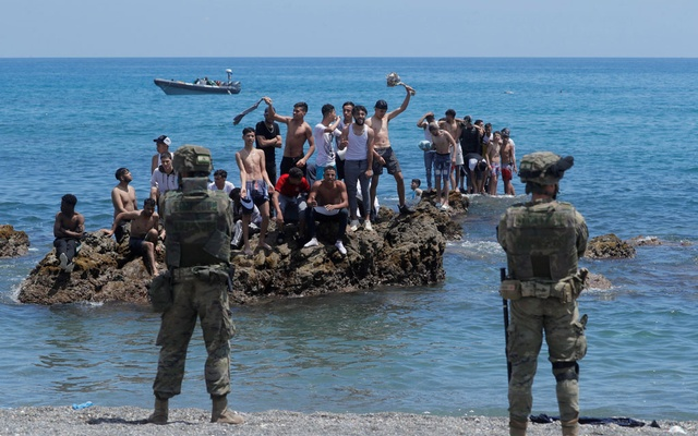 Moroccan citizens stand on the rocks in front of Spanish legionnaires at El Tarajal beach, near the fence between the Spanish-Moroccan border, after thousands of migrants swam across this border on Monday, in Ceuta, Spain, May 18, 2021. REUTERS