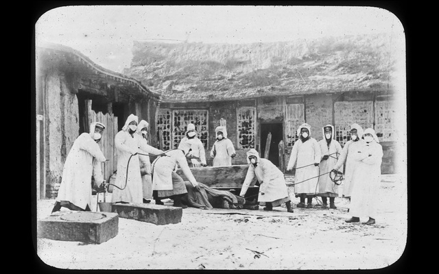 In an image provided by Harvard University, Countway Library of Medicine, health workers prepare a body of a plague victim for burial in Changchun, China, in 1911. Dr. Wu Lien-Teh helped change the course of a plague epidemic in the early 20th century and promoted the use of masks as a public health tool. (Harvard University, Countway Library of Medicine via The New York Times)