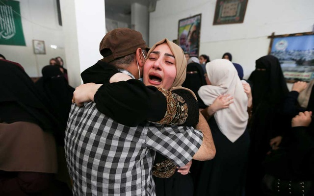 A woman mourns, as she attends a funeral of Palestinians killed during Israeli- Palestinian fighting, following Israel- Hamas truce, in Khan Younis, in the southern Gaza Strip, May 21, 2021. REUTERS
