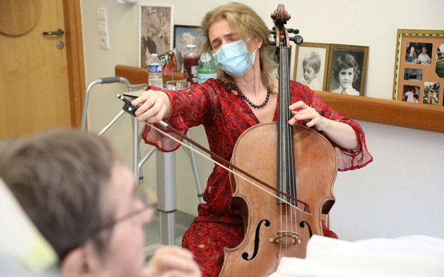 Cellist Claire Oppert plays music to soothe patient Bernard Genin, 79, at end-of-life care home Jeanne Garnier in Paris, France, May 21, 2021. REUTERS