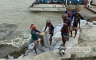 Workers stack sandbags to protect the Shimulia pier in Munshiganj on Wednesday, May 26, 2021, as the influence of Cyclone Yaas raises the Padma River's water level. Photo: Ahornish Ahona