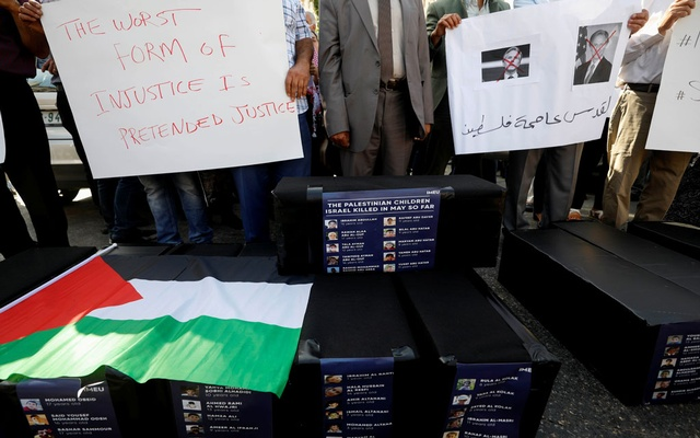 Demonstrators hold a sign with crossed-out pictures of US Secretary of State Antony Blinken as pictures of Palestinian children, killed during recent Israeli-Palestinian fighting in Gaza, are seen on mock coffins during a protest against the visit of Blinken, in Ramallah, in the Israeli-occupied West Bank May 25, 2021. REUTERS