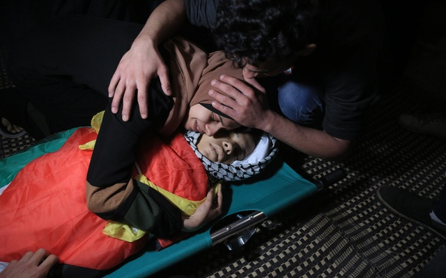 Nagham Tolbeh mourns over the body of her brother, Mahmoud, in Gaza City on May 14, 2021. The New York Times