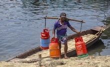 A worker carries empty cooking gas cylinders from a boat at Beribandh in Dhaka's Mirpur. Photo: Asif Mahmud Ove
