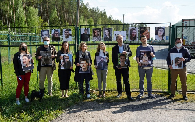 Press advocacy group Reporters Sans Frontiers activists and local journalists hold photos of journalists detained in Belarus at Salcininkai border crossing point, Lithuania on May 27, 2021. REUTERS