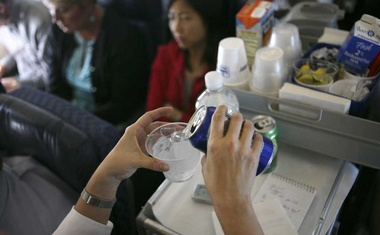 A soft drink is poured into a plastic cup of ice on a commercial airline flight in the US, July 15, 2008. Studies have shown that noise, low pressure, dry air, plastic cutlery and cups can alter the way we taste things at high altitude. Airlines are starting in earnest to tailor their offerings to account for those changes. (Ruth Fremson/The New York Times)