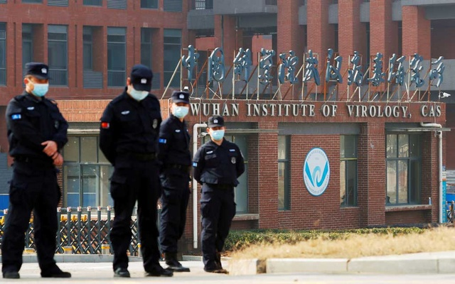 FILE PHOTO: Security personnel keep watch outside Wuhan Institute of Virology during the visit by the World Health Organization (WHO) team tasked with investigating the origins of the coronavirus disease (COVID-19), in Wuhan, Hubei province, China February 3, 2021. REUTERS/Thomas Peter/File Photo