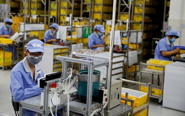 Employees wearing face masks work at a factory of the component maker SMC during a government organised tour of its facility following the outbreak of the coronavirus disease (COVID-19), in Beijing, China May 13, 2020. REUTERS
