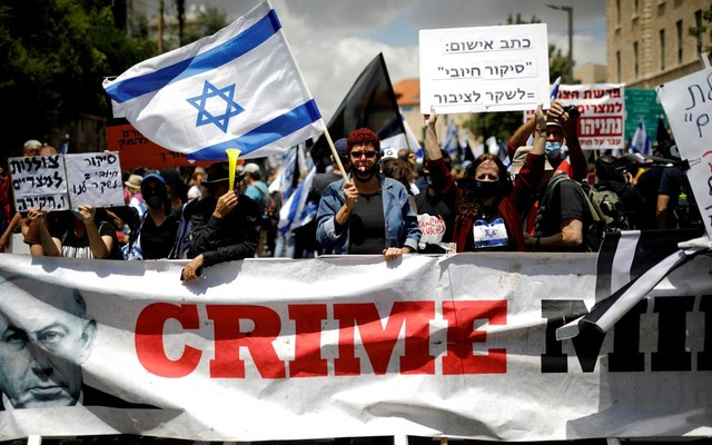 Protesters wave an Israeli flag and hold placards as they stand behind a banner reading,