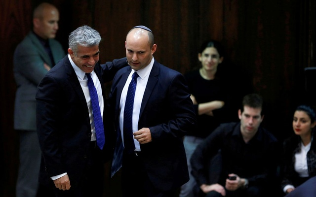 Israel's Finance Minister Yair Lapid (L) and Minister of Economics and Trade Naftali Bennett (2nd L) walk together during the swearing-in ceremony, at the Knesset, the Israeli Parliament, in Jerusalem March 18, 2013. Reuters