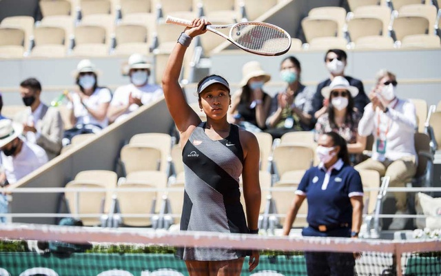 Naomi Osaka acknowledges the crowd following her win against Patricia Maria Tig in the first round of the French Open at Court Philippe Chatrier in Paris, May 30, 2021. Osaka won her opening match at the French Open, but was warned that she risked escalating penalties, including default, if she failed to fulfill her media obligations. (Pete Kiehart/The New York Times)