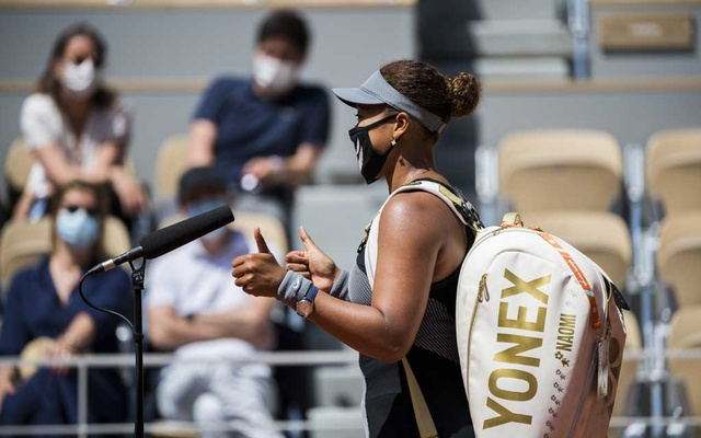 Naomi Osaka gives a thumbs-up during an on-court interview after her first round match against Patricia Maria Tig during French Open at Court Philippe Chatrier in Paris, May 30, 2021. Osaka won her opening match at the French Open, but was warned that she risked escalating penalties, including default, if she failed to fulfill her media obligations. (Pete Kiehart/The New York Times)