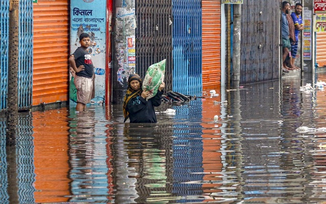 A woman wades through waist-deep water on the street outside Sayedabad Bus Terminal in Dhaka after incessant rains for hours on Tuesday, Jun 1, 2021.