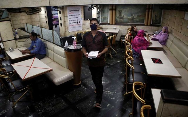 A waiter walks past tables that have been blocked to maintain social distancing at restaurant after they reopened amidst the spread of the coronavirus disease (COVID-19) in Mumbai, India, October 8, 2020. REUTERS/Francis Mascarenhas/File photo