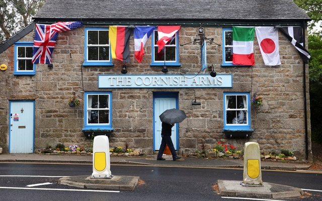 A person walks past The Cornish Arms pub as the G7 nations' flags flutter next to the Cornish flag, ahead of the G7 summit, in Carbis Bay, Cornwall, Britain, June 5, 2021. Reuters