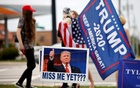Supporters of former US President Donald Trump gather on a street corner near a sign saying