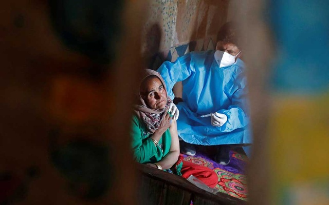 A shepherd woman is reflected as she receives a dose of COVISHIELD, a coronavirus disease (COVID-19) vaccine manufactured by Serum Institute of India, inside her hut during a vaccination drive at a forest area in south Kashmir's Pulwama district June 7, 2021. REUTERS/Danish Ismail/File Photo