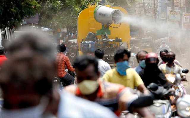 People wearing face masks ride motorcycles as a municipal vehicle decontaminates a road during a 21-day nationwide lockdown to slow the spreading of coronavirus disease (COVID-19), in Chennai, India, April 9, 2020. REUTERS/P. Ravikumar