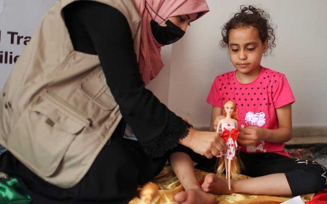 A psychologist plays with Palestinian girl Suzy Eshkuntana, who was pulled out from the rubble of her house, destroyed by an Israeli air strike during Israeli-Palestinian fighting, as part of a mental health support session in Gaza City, June 3, 2021. REUTERS/Mohammed Salem