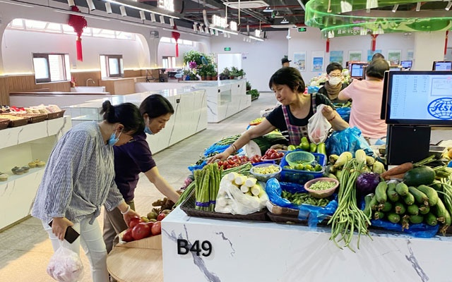Shoppers look at vegetables at an indoor market in Shanghai on May 27, 2021. The authorities have long used informal price controls and subsidies to prevent rising costs from being felt in China's supermarkets and at the family dinner table. The New York Times