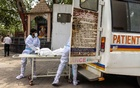 Health workers carry the body of a person, who died from complications related to the coronavirus disease (COVID-19), for cremation at a crematorium in New Delhi, India, Jun 10, 2021. REUTERS
