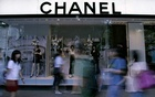 People walk past a Chanel display window at a shopping district in Singapore November 3, 2008. REUTERS