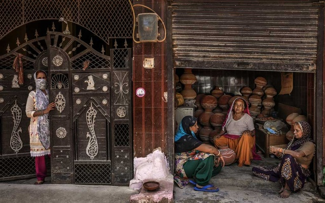 Shanno, second from right, at her pottery shop in New Delhi's Nangli Vihar neighbourhood, May 21, 2021. Shanno, who goes by one name, is desperate for an income. She has continued to open her shop every day throughout the coronavirus pandemic despite stigma. Atul Loke/The New York Times