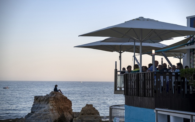Diners on a waterfront terrace in Albufeira, a beach town in the Algarve, Portugal's leading tourist destination, Jun 4, 2021. James Hill/The New York Times