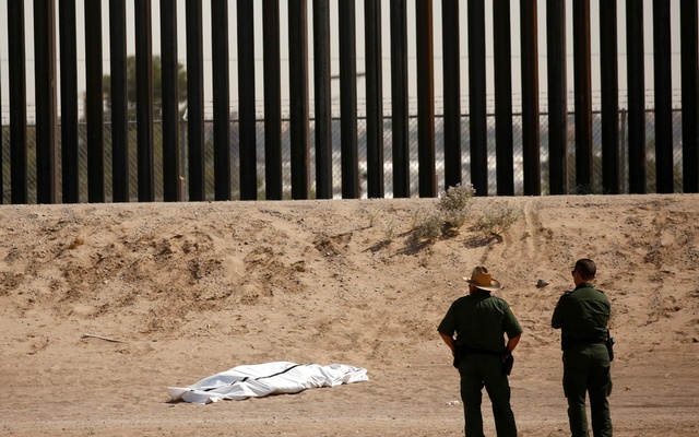 US Border Patrol agents observe the body of a person covered in a white sheet near the border wall in El Paso, Texas, US, as seen from Ciudad Juarez, Mexico Jun 11, 2021. REUTERS