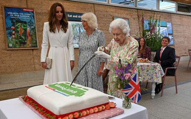 Britain's Queen Elizabeth attempts to cut a cake with a sword next to Camilla, Duchess of Cornwall, and Catherine, Duchess of Cambridge as they attend a drinks reception on the sidelines of the G7 summit, at the Eden Project in Cornwall, Britain June 11, 2021. Oli Scarff/Pool via REUTERS