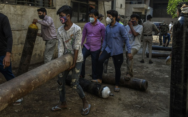Men carry empty oxygen cylinders back to a factory in New Delhi, May 9, 2021. Prime Minister Narendra Modi's efforts to squelch dissent and to accentuate the positives may not be able to counter widespread anger over his government's stumbling response to the pandemic. (Atul Loke/The New York Times).