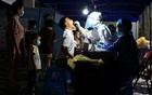 A medical worker in a protective suit collects a swab from a man for nucleic acid testing in Xiangzhou district of Zhuhai, following the coronavirus disease (COVID-19) outbreak in Guangdong province, China June 8, 2021. Picture taken June 8, 2021. China