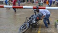 A motorcyclist slides his vehicle under the lowered boom barrier of the rail crossing at Dhaka's Tejgaon on Sunday, June 13, 2021. The crossing is currently closed due to construction work on the elevated expressway. Photo: Asif Mahmud Ove