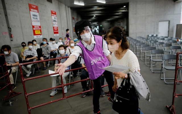 A woman is escorted by a staff member as she arrives to receive a dose of the coronavirus disease (COVID-19) vaccine at the Noevir Stadium Kobe, home venue of Japanese professional soccer club Vissel Kobe and currently acting as a large-scale COVID-19 vaccination centre, in Kobe, Japan June 12, 2021. Reuters