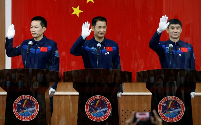 Chinese astronauts Nie Haisheng, Liu Boming, and Tang Hongbo wave as they meet members of the media behind a glass wall before the Shenzhou-12 mission to build China's space station, at Jiuquan Satellite Launch Centre near Jiuquan, Gansu province, China June 16, 2021. REUTERS